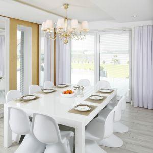 Przestronną jadalnię urządzono w bieli. Jej wytworny charakter podkreślają złote dodatki. Projekt Dominik Respondek. Fot. Bartosz Jarosz.