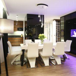 Przestronną jadalnię urządzono między kuchnią a salonem. Organizuje ją duży stół przy którym ustawiono tapicerowane krzesła. Projekt Monika i Adam Bronikowscy. Fot. Bartosz Jarosz.