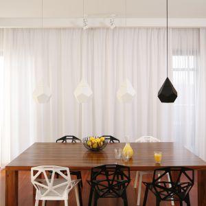 W otwartej strefie dziennej dominuje minimalizm. Stąd jadalnię organizuje jedynie drewniany stół, wokół którego ustawiono designerskie krzesła. Ich nowoczesna formę podkreślają lampy. Projekt Katarzyna Kiełek, Agnieszka Komorowska-Różycka. Fot. Bartosz Jarosz.