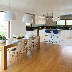 Przestronna jadalnia została połączona z kuchnią. Jej centrum stanowi duży, masywny stół, który zdobią designerskie krzesła projektu Eamesów. Projekt Małgorzata Galewska. Fot. Bartosz Jarosz.
