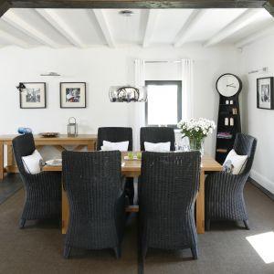 W urządzonym w marynistycznym klimacie wnętrzu jadalnia zajmuje centralne miejsce między kuchnią a salonem. Organizuje ją duży drewniany stół oraz ustawione przy nim wiklinowe krzesła. Projekt Kamila Paszkiewicz. Fot. Bartosz Jarosz.