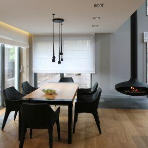 Przestrzeń jadalni organizuje duży drewniany stół przy którym dumnie prezentują się czarne wygodne krzesła. Można z nich podziwiać nie tylko ogień palący się w designerskim kominku, ale i piękne widoki za oknem. Projekt Katarzyna Kiełek, Agnieszka Komorowska-Różycka. Fot. Bartosz Jarosz.