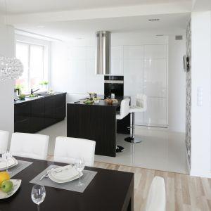 Przestronną kuchnię urządzono w minimalistycznym stylu. Jej jedyne wyposażenie stanowi wysoka zabudowa oraz kontrastująca z nią kolorystycznie wyspa. Projekt Karolina i Artur Urban. Fot. Bartosz Jarosz.