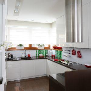 Częściowo otwartą przestrzeń kuchni urządzono w eleganckiej bieli. Jej salonowy charakter wydobywa zdobna fototapeta, którą wyłożono ściany nad blatem pod oknami. Projekt Katarzyna Mikulska-Sękalska. Fot. Bartosz Jarosz.