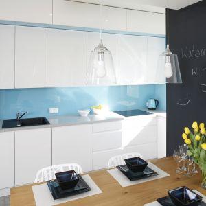 W białej kuchni zdecydowano się na niebieskie szkło na ścianę nad blatem. Projekt Agnieszka Zaremba, Magdalena Kostrzewa-Świątek. Fot. Bartosz Jarosz.