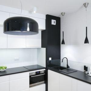 Kuchnię w bloku urządzono w bieli. Stanowi ona nowoczesne tło dla klasycznego w formie drewnianego stołu. Projekt Ewelina Para. Fot. Bartosz Jarosz.