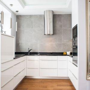 Biała zabudowa kuchenna zaprojektowana została w kształcie litery U. Pozwoliło to w pełni wykorzystać nieduża przestrzeń. Zrezygnowano tu  także z szafek górnych na rzecz wysokiej zabudowy umieszczonej na jednej ze ścian. Projekt Arkadiusz Grzędzicki. Fot. Adam Ościłowski, panadam.pl