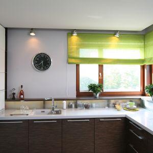 Kuchnię od jadalni oddzielają przesuwne drzwi z białego szkła. Po ich rozsunięciu z jadalni można podziwiać elegancką kuchnię, w której biel ociepla drewno. Projekt Magdalena Konopka, Maciej Konopka, Fot. Bartosz Jarosz.