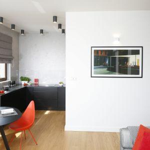 Kuchnia otwarta na salon daje wiele swobody jej użytkownikom. Brak górnej zabudowy optycznie powiększa przestrzeń, zaś czarne meble połączone z otynkowaną ścianą, przypominającą w wyglądzie beton nawiązują do stylu industrialnego. Projekt Małgorzata Łyszczarz. Fot. Bartosz Jarosz.