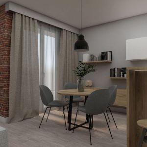 Zróżnicowane materiały, typowo pokojowe otwarte półki i szafka, dużo drewna oraz miękkie tkaniny w oknach nadają aneksowi kuchenno-jadalnemu salonowy charakter.