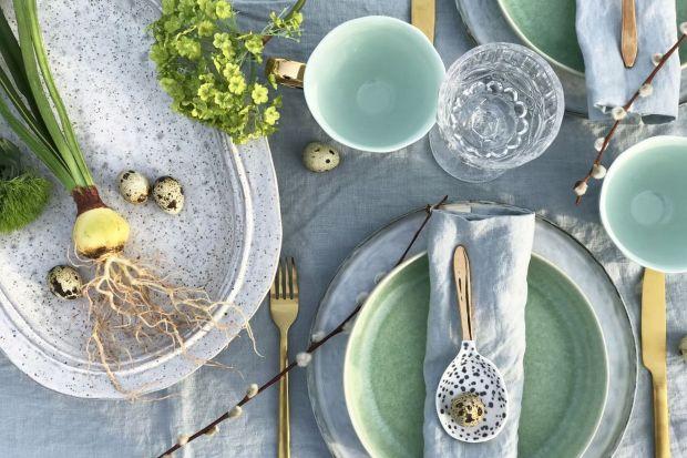 Ceramiczne naczynia w kilku pastelowych kolorach, złote sztućce i przystrojony zielenią biały obrus – to przepis na wiosenny, radosny i nastrajający optymistycznie stół.