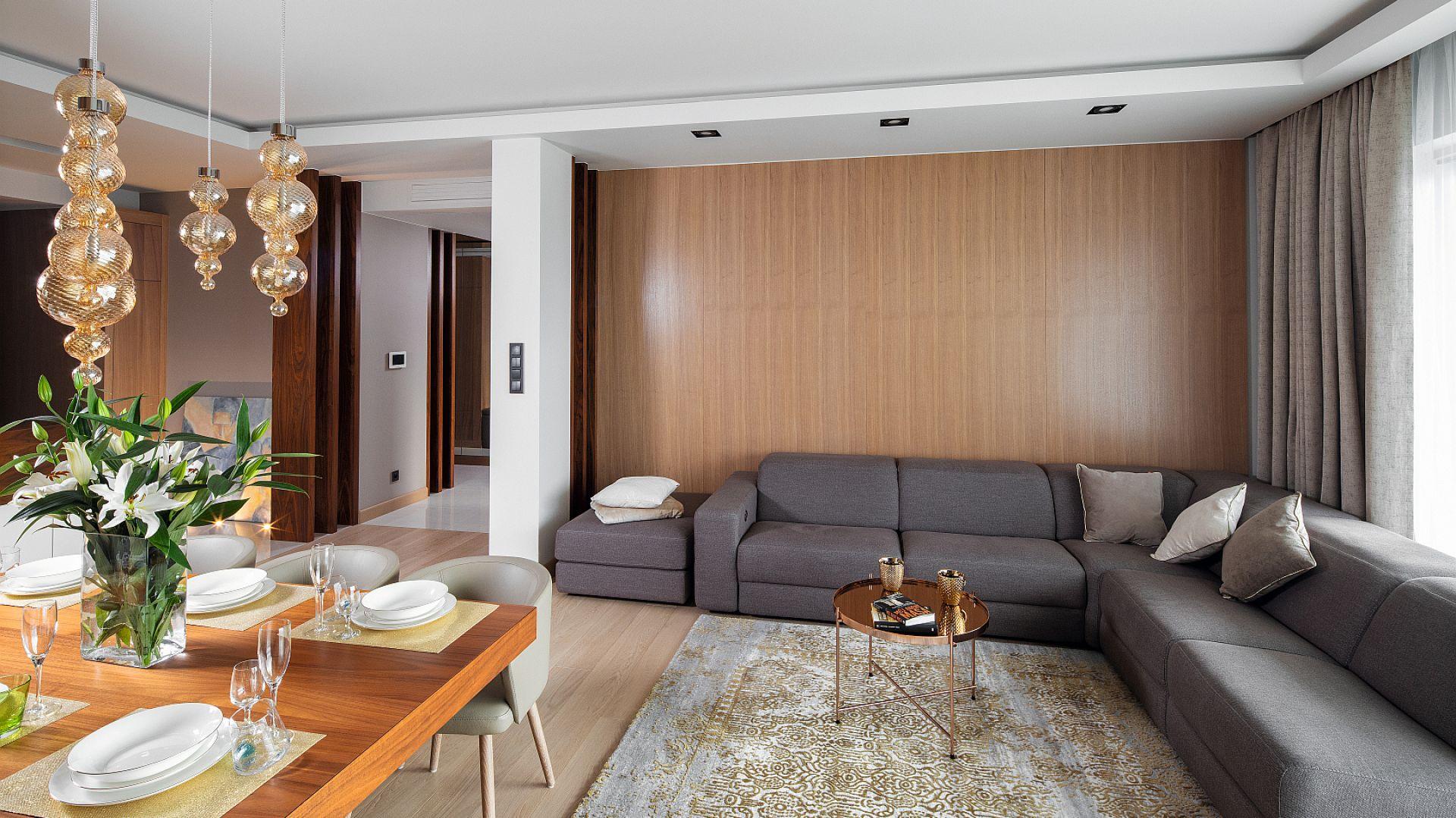 Dębowy fornir na ścianie za kanapą zastępuje zbędne dekoracje w salonie. Prezentuje się pięknie i stylowo, wprowadzając do wnętrza przytulny, elegancki klimat. Projekt: Laura Sulzik. Fot. Bartosz Jarosz