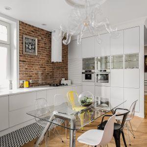 Czerwona cegła zdobiąca całą ścianę w kuchni doskonale kontrastuje z minimalistyczną, białą zabudową. Tam, gdzie było to konieczne ze względów praktycznych, cegłę zabezpieczono szkłem, które pozostaje całkowicie niewidoczne. Projekt: Anna Maria Sokłowska. Fot. Foto&Mohito