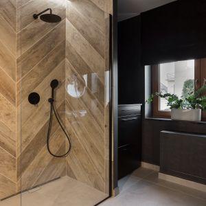 Ścianę w strefie prysznica zdobią drewnopodobne płytki ułożone w klasyczną jodełkę. Projekt: Katarzyna Maciejewska. Fot.  Anna Laskowska, Dekorialove