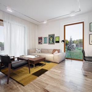 Salon urządzony jest z dużym smakiem. Białe ściany dobrze komponują się z naturalnym drewnem na podłodze. Całość zdobią modne, kolorowe grafiki i nowoczesne meble. Projekt: Galia. Fot. Archetyp