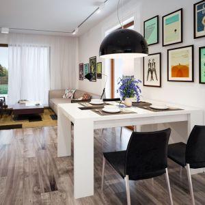 Pomiędzy kuchnia i salonem wygospodarowano miejsce na niewielką jadalnię. Biały stół w połączeniu z czarnymi krzesłami i ciemną lamą prezentuje się niezwykle elegancko. Projekt: Galia. Fot. Archetyp