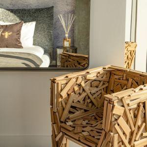 """Apartament Nature. Fotel zbudowany jest z wielu drewnianych listewek, podobnych do klasycznej sklejki, które w zamyśle twórcy miały przypominać deski używane do budowy brazylijskich """"faweli"""". Fot. Łukasz Zandecki"""
