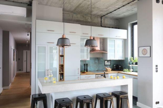 Urządzone w loftowym klimacie wnętrze zyskało odrobinę domowej przytulności za sprawą otwartej kuchni, która – choć wpisująca się w industrialną stylistykę – dodała wnętrzom lekkości i kobiecego charakteru.