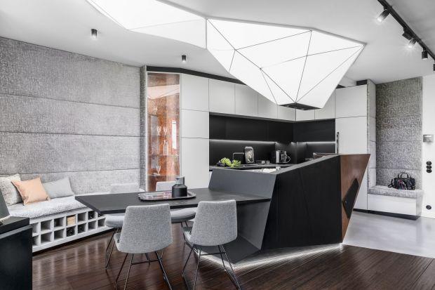 Główną rolę w aranżacji kuchni odgrywa futurystyczna bryła wyspy oraz górująca nad nią podświetlana instalacja, które nadają wnętrzu awangardowy charakter. Mnogość zastosowanych materiałów tworzy jednocześnie przytulną i ciepłą atmosf