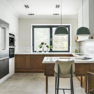 Urządzona w bieli i drewnie kuchnia została zaprojektowana z myślą o komfortowym użytkowaniu – przygotowaniu oraz wspólnym spożywaniu posiłków. Dom na jeziorem. Projekt JT Grupa, Zdjęcia Tom Kurek