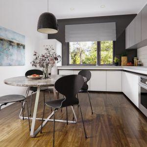 """Kuchnia z zabudową na planie litery """"L"""" to zgrabne połączenie bieli i szarości. Duże okno dodatkowo rozświetla przestrzeń. Fot. Archetyp"""