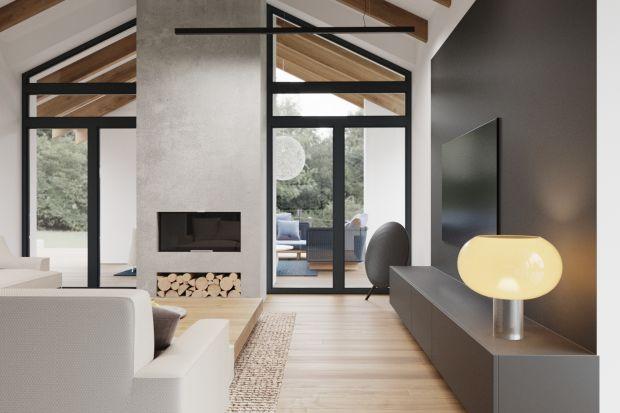 Minimalistycznych charakter wnętrza ociepla drewno w dwóch różnych odcinaniach, które pięknie łączy się z bielą, betonem, tkanymi meblami oraz delikatnym oświetleniem. Dzięki temu przestrzeń jest nie tylko elegancka, ale i przytulna.