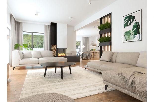 Dom pod Poznaniem charakteryzuje nowoczesna aranżacja. Jasne kolory i proste współczesne meble oraz masa naturalnego światła nadają wnętrzu lekkości. Ale do relaksu zapraszają przede wszystkim dwie obszerne sofy.