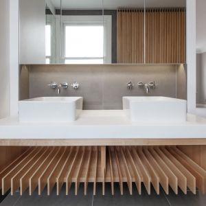 Jasną łazienkę ocieplają drewniane elementy. Fot. Nick Leith-Smith