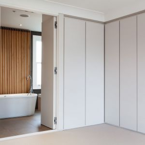 Drzwi do łazienki są na pierwszy rzut oka niewidoczne. Zlewają się z szafami tworząc z nimi spójną całość. Fot. Nick Leith-Smith