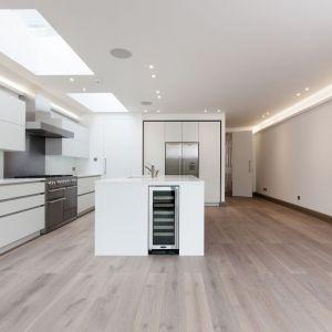 Kuchnię z wyspą urządzono w minimalistycznym, nowoczesnym stylu. Dzięki temu wnętrze jest bardzo przestronne i funkcjonalna. Fot. Nick Leith-Smith