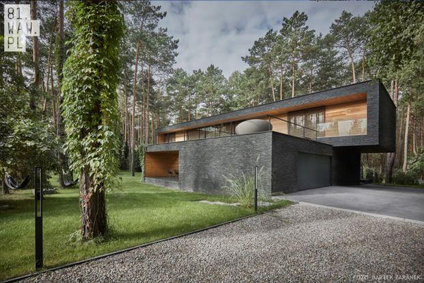 Kamienna elewacja domu Leśnego nawiązuje do ciemnych pni sosen, które rosną na tym terenie. Natomiast wrażenie masywności czarnej bryły minimalizują wnęki, które zostały wykończone jasnym drewnem.
