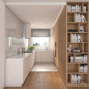 Niską zabudowę z kształcie litery L uzupełnia szafa na całą ścianę, w której oprócz mnóstwa schowków zmieścił się sprzęt AGD. W części kuchni, gdzie przygotowuje się posiłki, na podłodze położono łatwy do utrzymania w czystości gres. W reszcie pomieszczenia jest drewniana deska, który łączy wizualnie kuchnię z salonem. Fot. Pracownia MGN