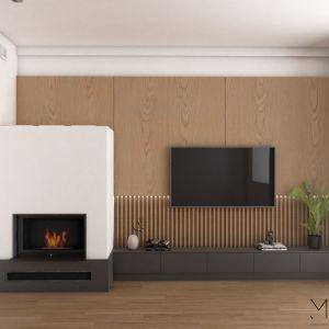 Drewniana okładzina ściany z pełnych płyt i listewek oraz kominek o nietypowym, przyciągającym wzrok kształcie tworzą w salonie bardzo przytulny nastrój. Fot. Pracownia MGN