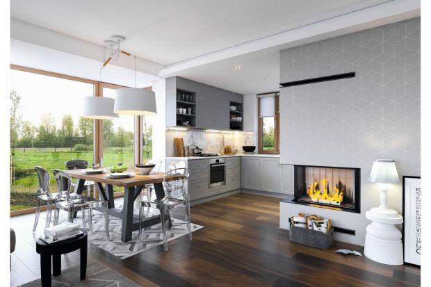 Oto, jak prezentuje się kuchnia z jadalnią w polskim, nowoczesnym domu. Niewątpliwą atrakcją tej wspólnej przestrzeni jest kominek, idealnie pasujący do stylu wnętrza.