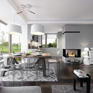 Białe, minimalistyczne wnętrze ociepla drewniana podłoga w odcieniu czekolady. Meble i elementy oświetlenia są dekoracją samą w sobie. Fot. Domy z Wizją