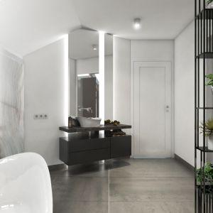 Miejsce przy drzwiach przeznaczono na umywalkę o takiej samej formie, co wanna. Wspiera się ona na kamiennym blacie. Pod nim – pojemna szafka na ręczniki i kosmetyki. Fot. Pracownia Architektoniczna MGN