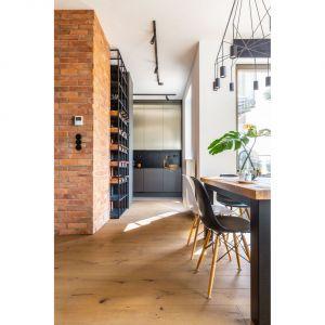 Niezbędny w wykończeniu loftu metal, m.in. listwy oświetleniowe, lampa nad stołem, regały na wino i książki, są w kolorze czarnym. Fot. Decoroom