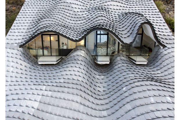 """Rzut oka na dom i uwagę przykuwa oryginalny, pofalowany kształt dachu, który został wykonany z metalu i pokryty powłoką cynkową. Inspiracją przy jego tworzeniu były fale morskie oraz... łuski smocze. Cynkowe """"płytki łuski"""" pokrywają"""