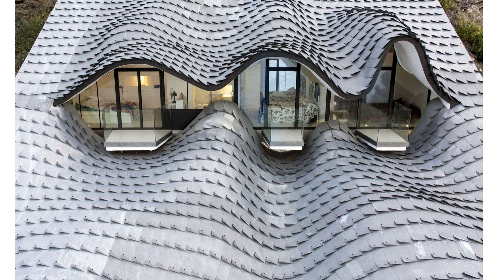 Rzut oka na dom i uwagę przykuwa oryginalny, pofalowany kształt dachu, który został wykonany z metalu i pokryty powłoką cynkową. Inspiracją przy jego tworzeniu były fale morskie oraz... łuski smocze. Fot. Jesus Granada