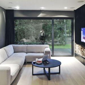 Duże przeszklenia w domu zlokalizowanym w lesie są niezwykle ważne, ponieważ doświetlają pomieszczenia. Dzięki nim również las przenika do wnętrza, tworząc piękne, naturalne obrazy. Fot. zw A