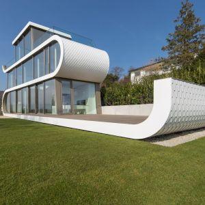 Zakrzywiona dynamiczna konstrukcja ścian, otwarta przestrzeń i duże przeszklenia tworzą niepowtarzalny charakter Flexhouse. Fot. Peter Wuermli