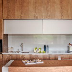 Urozmaiceniem fornirowanej kuchni jest wprowadznie elementów lakierowanych, jak w modelu Z5. Ważne jest to, by lakier subtelnie przełamywał ciepły kolor drewna, a w tej roli świetnie sprawdzi się paleta szarości i grafitów. Fot. Zajc
