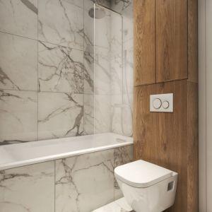 W aranżacji łazienki połączono drewno z pięknymi, imitującymi marmur płytkami, które nadają wnętrzu  luksusowy wygląd. Projekt i zdjęcia: Pracownia Architektoniczna MGN