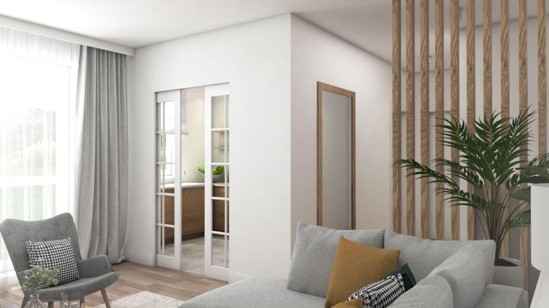 Przesuwane, niemal całkowicie przeszklone drzwi  łączą optycznie kuchnię z pokojem. Projekt i zdjęcia: Pracownia Architektoniczna MGN