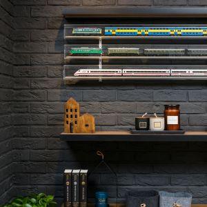 Pomalowana na grafitowy kolor cegła na ścianie dodaje przestrzeni wyrazu i stanowi efektowne tło dla kolekcji modeli pociągów. Projekt: Katarzyna Krupa. Fot. Stan Zajączkowski