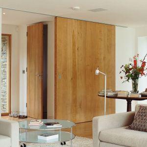 Ciekawym rozwiązaniem są duże, przesuwne, drewniane drzwi oddzielające salon od strefy wejściowej. Architekt: McLean Quinlan