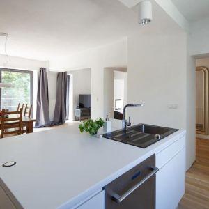 Białe ściany, sufity i meble kuchenne sprawiają, że całe wnętrze wydaje się przestronne. Drewniane elementy ocieplają pomieszczenia. Fot. Tomasz Zakrzewski