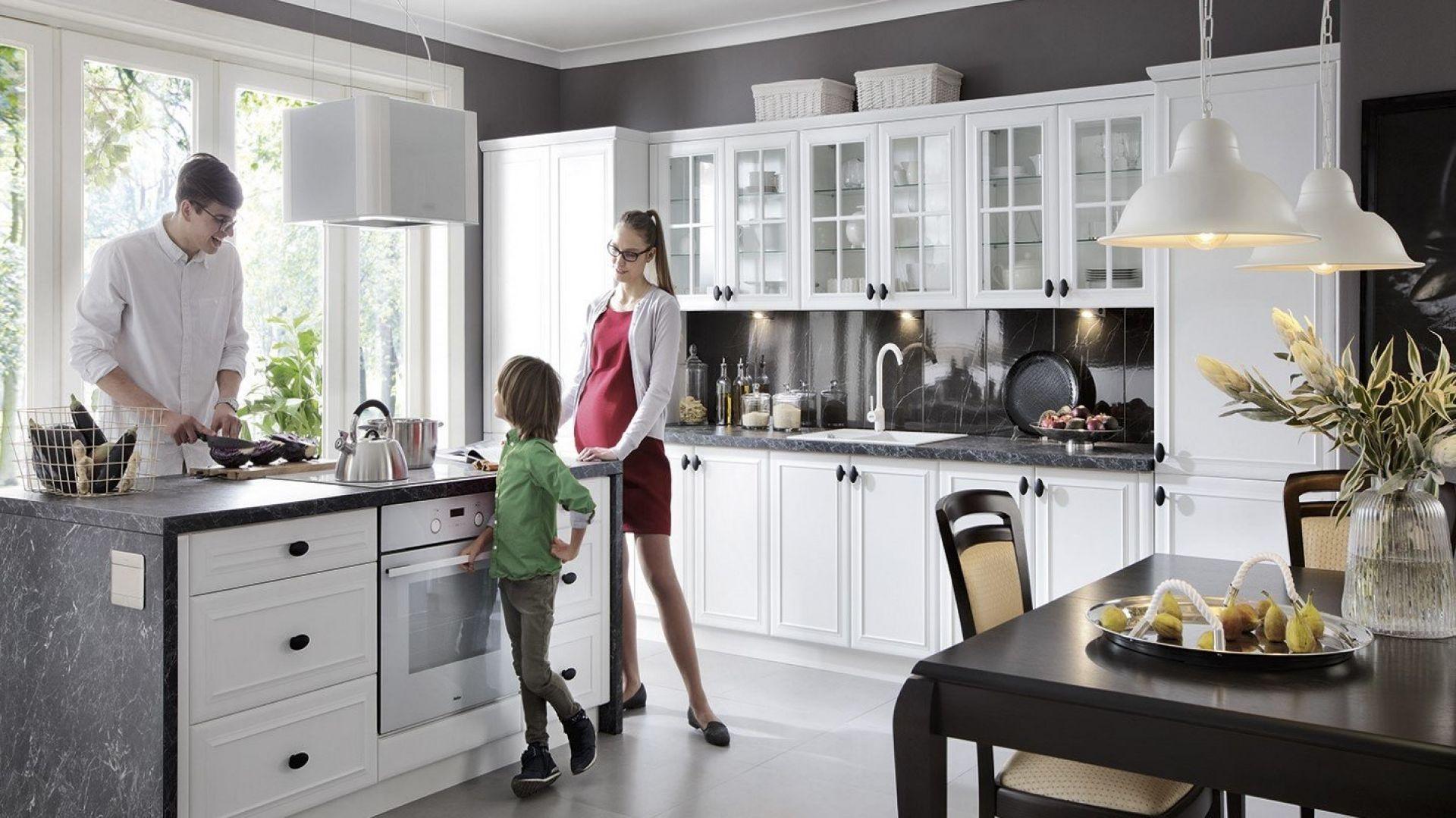 Kuchnia modułowa Family Line Fiore. Fronty w odcieniu biały super mat z dekoracyjnym frezowaniem to kwintesencja elegancji i szyku. Przywodzą na myśl szlachetne, angielskie wystroje, w których ducha tradycji wyczuwa się w każdym detalu. Meble dostępne w ofercie firmy Black Red White. Fot. Black Red White