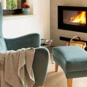 Wygodny fotel przy kominku jest idealnym miejscem na lekturę ulubionych książek. Fot. www.makehome.pl