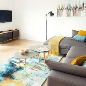 Ponieważ salon jest sercem każdego domu, a domownikom zależało na dużej kanapie, postawiono na wygodny i funkcjonalny narożnik. Fot. www.makehome.pl